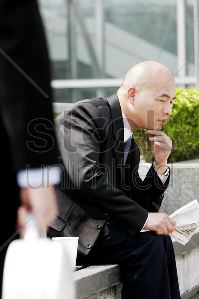 a bald man sitting on the bench thinking stock photo