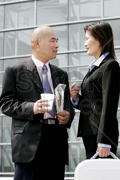 a bald man talking to a woman stock photo