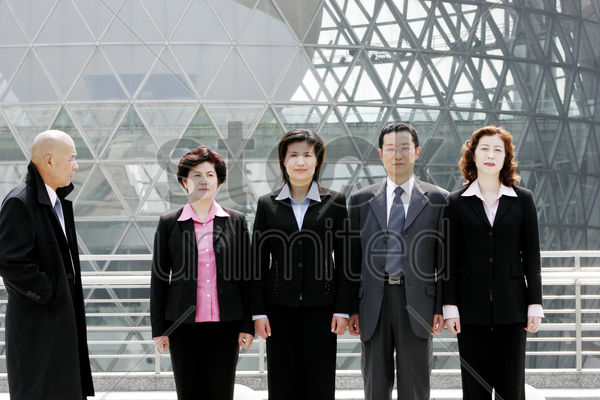 a bald man watching a group of business people standing in a row stock photo