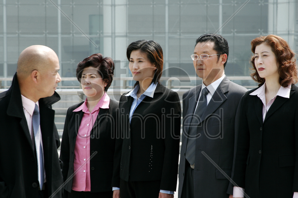 a bald man watching his employees standing at attention stock photo