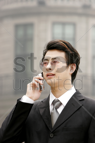 a bespectacled businessman talking on the hand phone stock photo