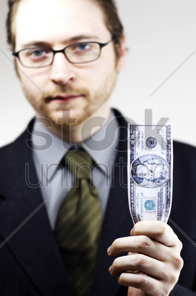 a bespectacled man in business suit holding a banknote stock photo