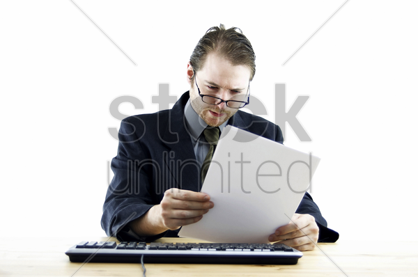 a bespectacled man in business suit sitting at his desk reading some notes stock photo