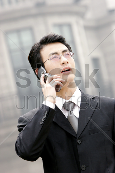 a bespectacled man in business suit talking on the hand phone stock photo