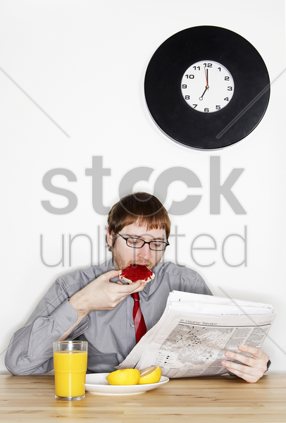 a bespectacled man in working attire reading newspaper while having his breakfast stock photo