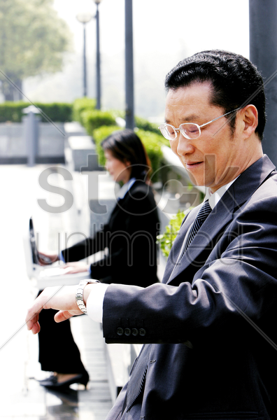 a bespectacled man looking at his watch while a woman using her laptop stock photo