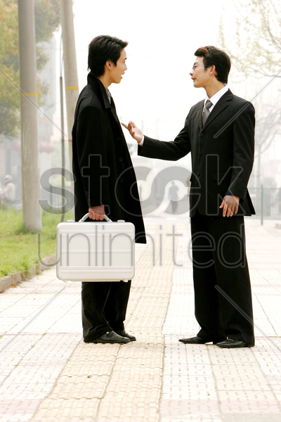 a bespectacled man scolding his colleague stock photo