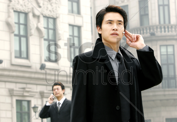 a bespectacled man talking on the hand phone while another man talking using bluetooth stock photo
