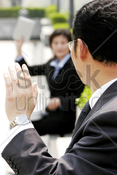 a bespectacled man waving to a woman stock photo