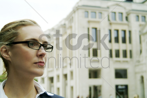 a bespectacled woman standing in front of a building stock photo