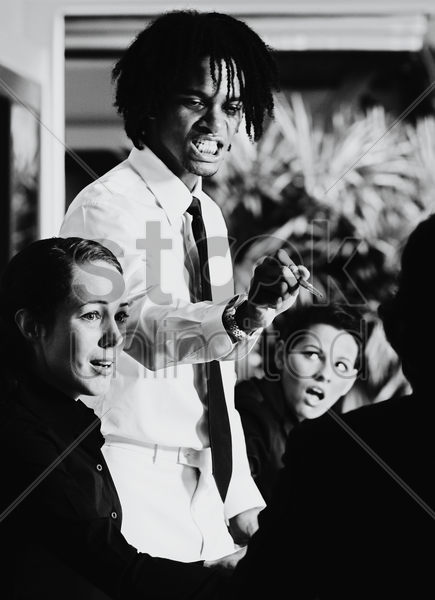 a black and white picture of an angry african american man scolding his colleague in a meeting stock photo