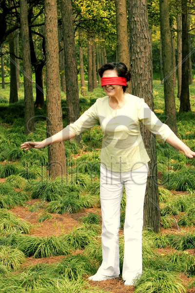 a blindfolded woman trying to find her way stock photo