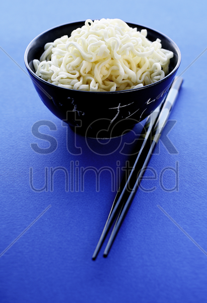 a bowl of noodles and chopsticks stock photo