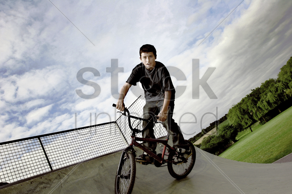 a boy cycling in a skateboard park stock photo
