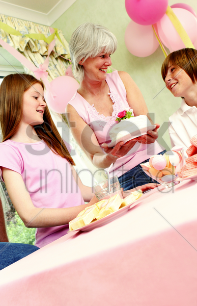 a boy looking at his mother as she brings out the birthday cake for his sister stock photo