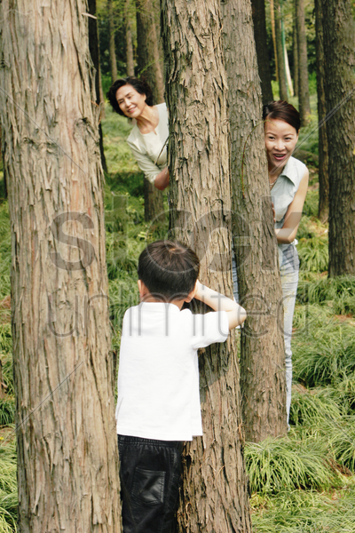 a boy playing hide and seek with his mother and grandmother in the forest stock photo