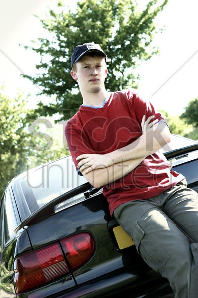 a boy with cap leaning against a car stock photo