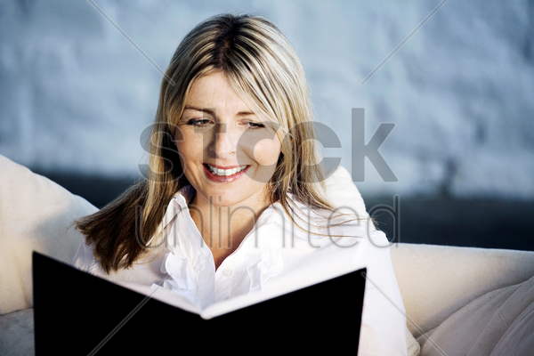 a business lady smiling while reading stock photo
