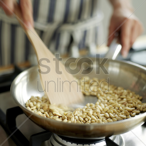 a chef using a spatula to fry nuts stock photo