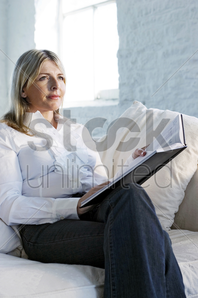 a confident looking business lady sitting on a couch stock photo