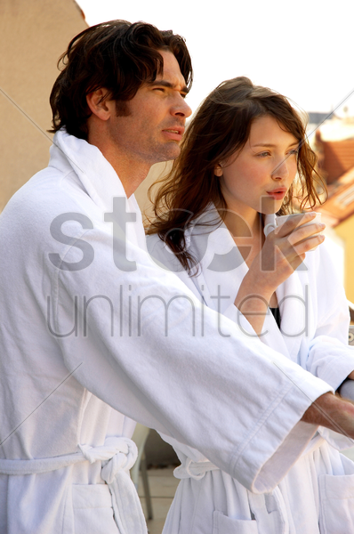 a couple in bathrobes standing on the balcony stock photo