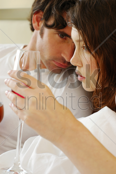 a couple lying on the bed drinking wine stock photo