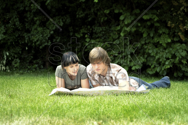 a couple lying on the grass analyzing a map stock photo
