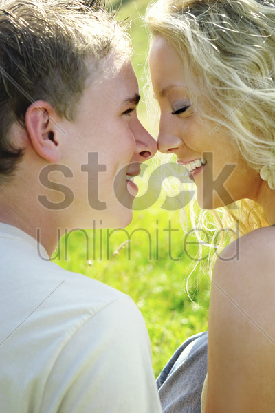 a couple nose rubbing in the field stock photo