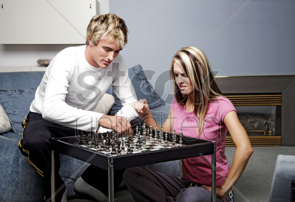 a couple playing chess stock photo