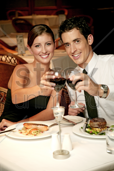 a couple showing a toast to the camera stock photo
