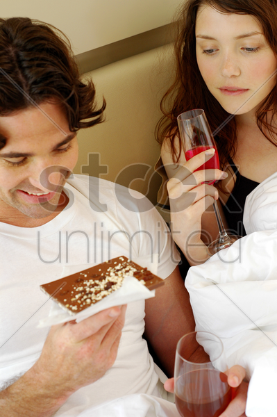 a couple sitting on the bed eating and drinking stock photo