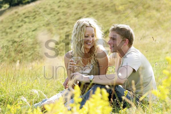 a couple sitting on the prairie chatting stock photo