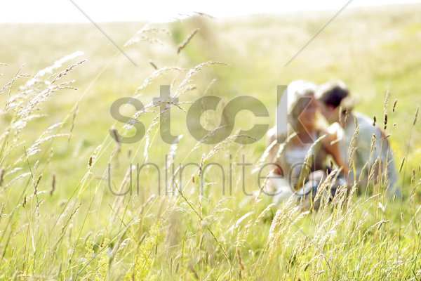 a couple sitting together on the prairie stock photo