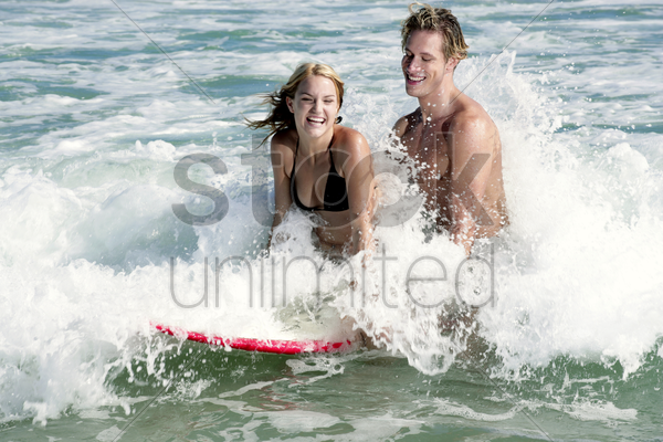 a couple surfing together on the sea stock photo