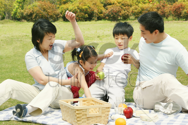a family picnicking in the park stock photo