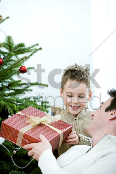 a father giving a christmas present to his son stock photo