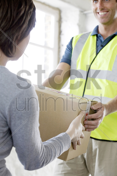 a friendly delivery man passing over a parcel to customer stock photo