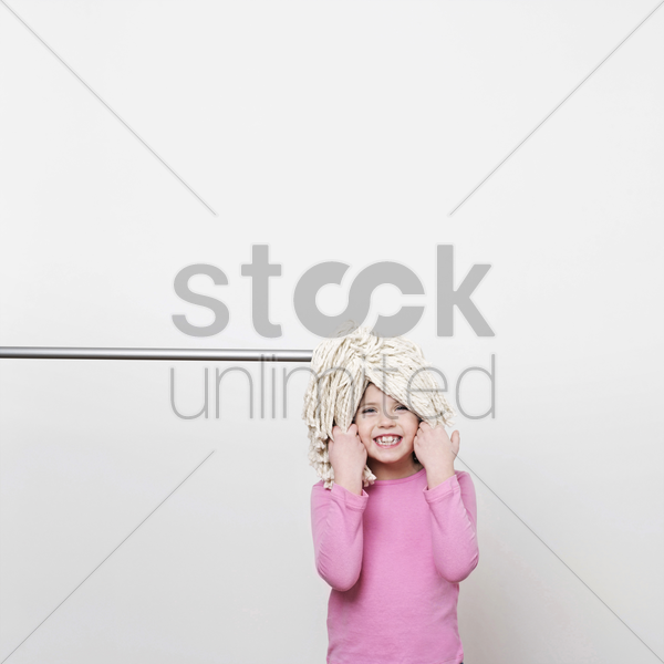 a girl (5-7) with a mop on her head stock photo