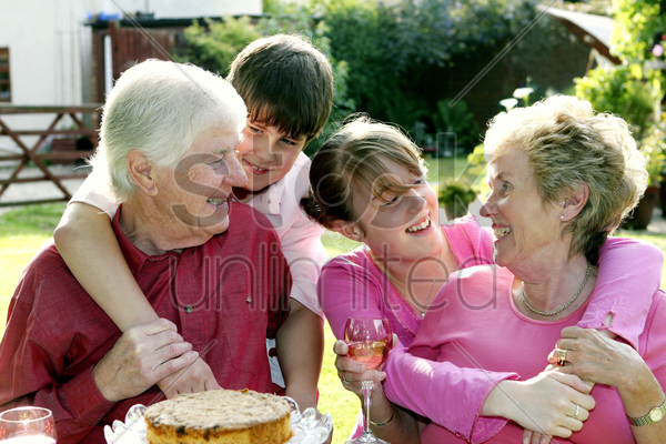 a girl and boy giving their grandparents a surprise visit stock photo
