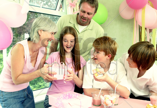 a girl happily receiving her birthday present from her mother while the others watching stock photo