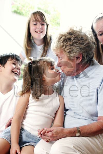 a girl kissing her grandmother whiles her brother and sisters watching stock photo