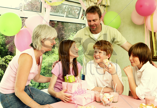 a girl looking happy to receive gifts from her parents and siblings stock photo