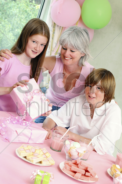 a girl opening her birthday presents stock photo