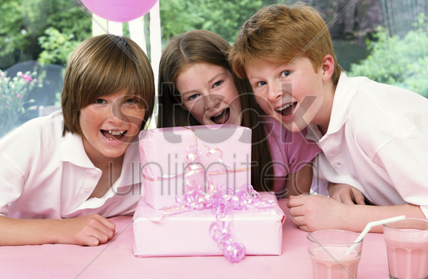 a girl posing with her brothers in front of her birthday presents stock photo