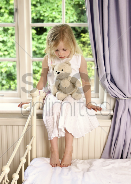a girl sitting by the window with a teddy bear on her lap stock photo