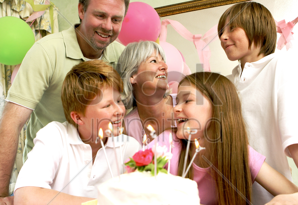 a girl sitting in front of her birthday cake with her parents and siblings surrounding her stock photo
