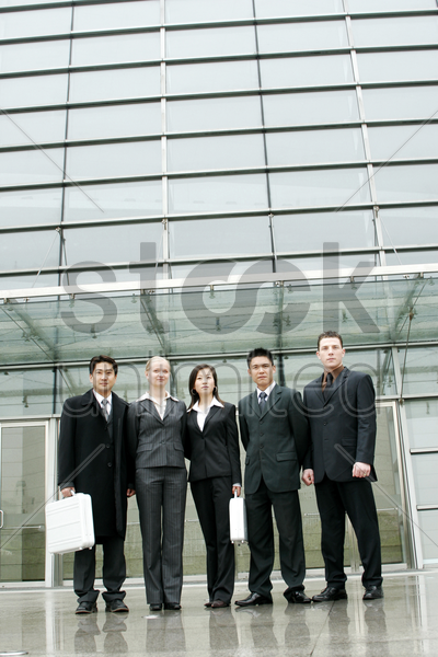 a group of business people standing in front of their office building stock photo