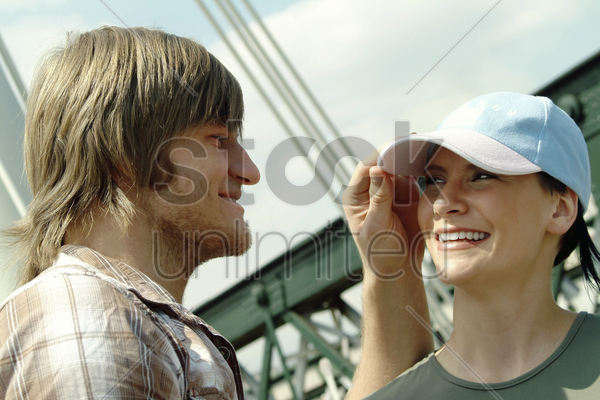 a guy adjusting his girlfriend's cap stock photo