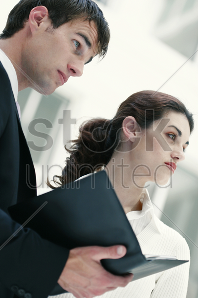 a guy and lady looking away while reading a document stock photo