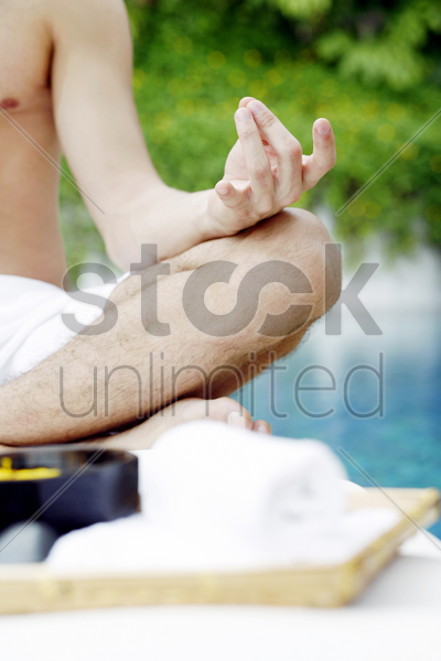 a guy doing meditation at the poolside stock photo
